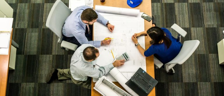 A group of engineers at a table discussing a blueprint.