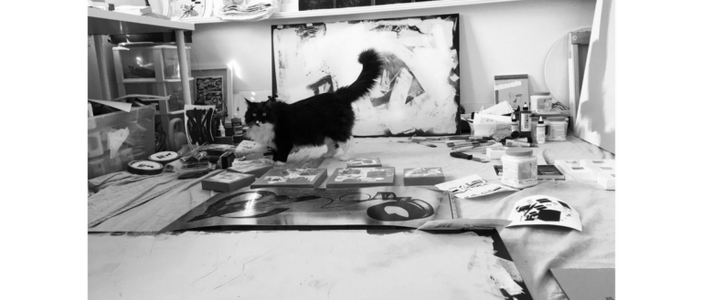 A photograph of a cat on art supplies by Elizabeth Bagwell.