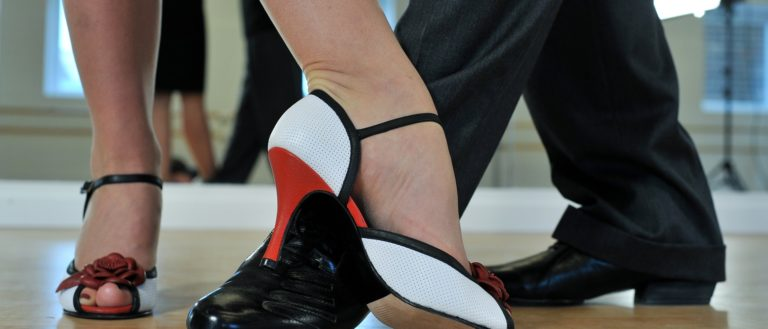 The feet of a man and woman during a tango dance.