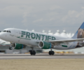 A Frontier Airlines aircraft departing the runway.