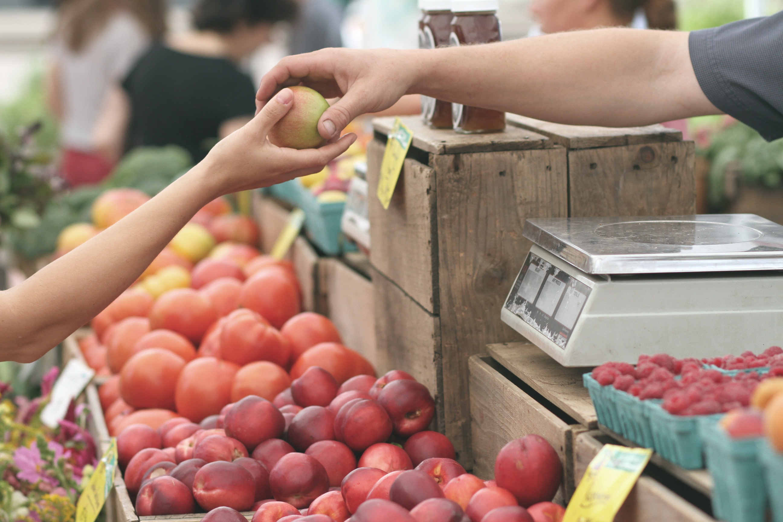 A person buying an apple at a farmers market.