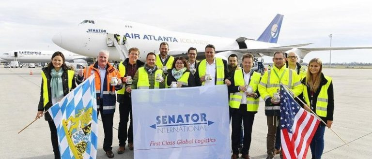 Employees of Senator International celebrating new success in front of one of their cargo planes.