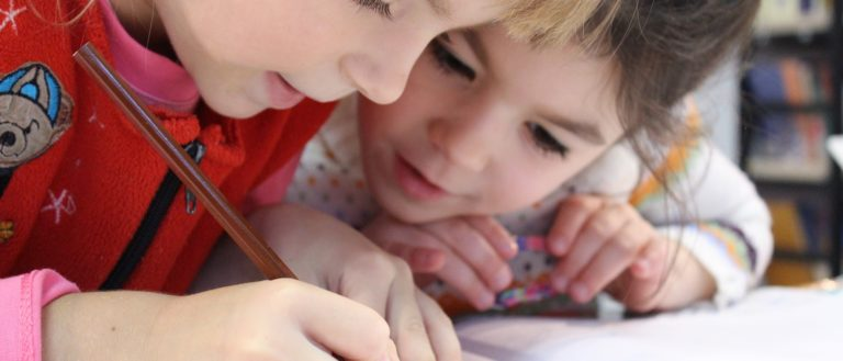 Two children writing in a book at school.
