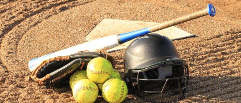 Softball equipment on the ground in front of home plate.
