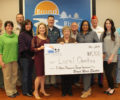Broad River Electric employees holding a check for charity donation.