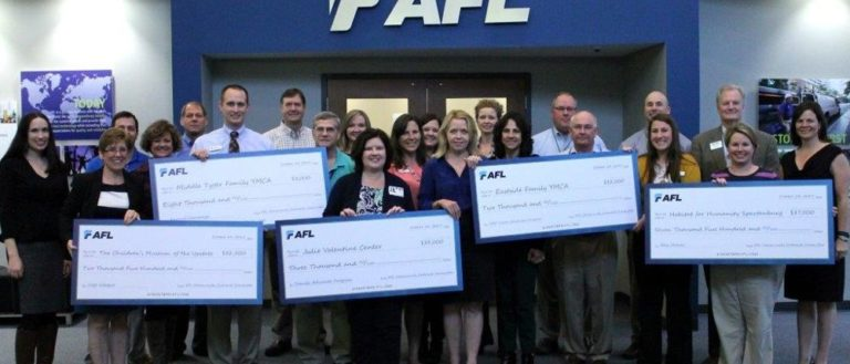 AFL employees holding a set of checks for local nonprofits.