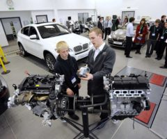 BMW Group employee demonstrating inner workings of an engine to a student.