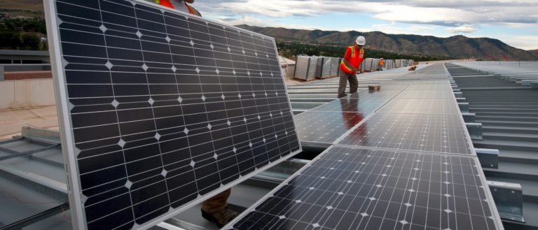 Workers installing solar panels on the roof of a building.