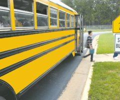 Children exiting a schoolbus at a school bus stop.